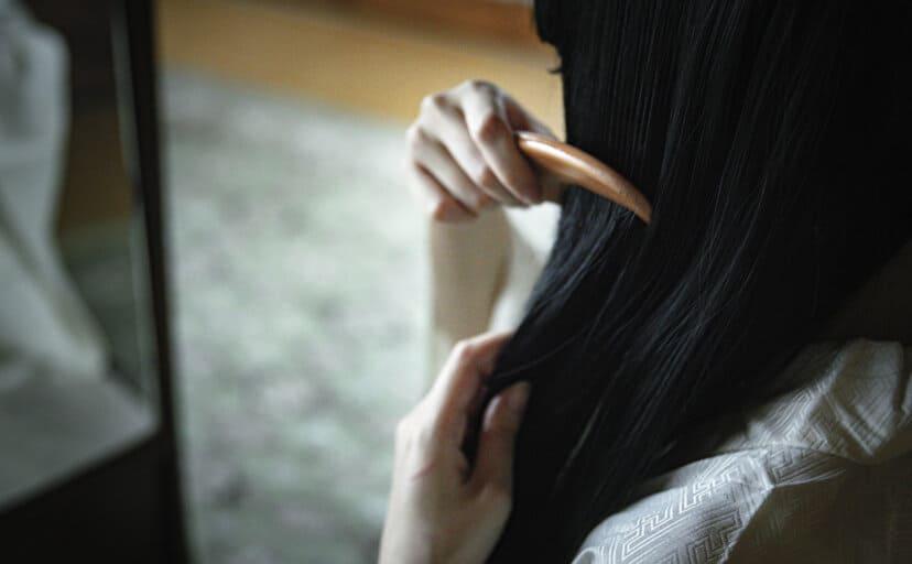 櫛で髪をとかす女性(フリー写真)